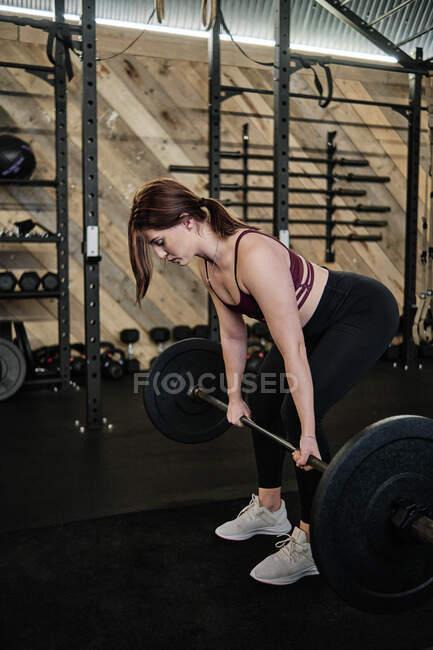 Vista lateral de una mujer en forma levantando pesas, haciendo ejercicio en el gimnasio. tiro vertical - foto de stock