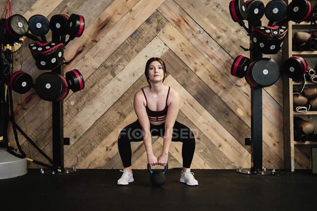 Молода жінка, що вправляється, підіймає кетлебел на самоті у спортзалі. — стокове фото