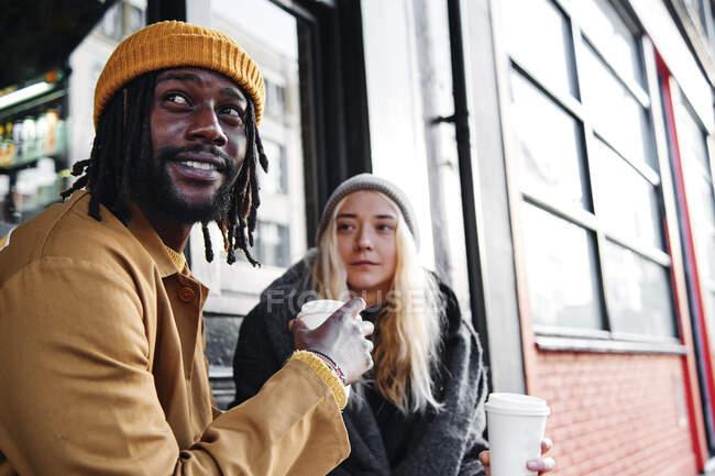 Couple multiracial à la mode assis à l'extérieur en buvant du café. amoureux biraciaux sur le concept de date. — Photo de stock