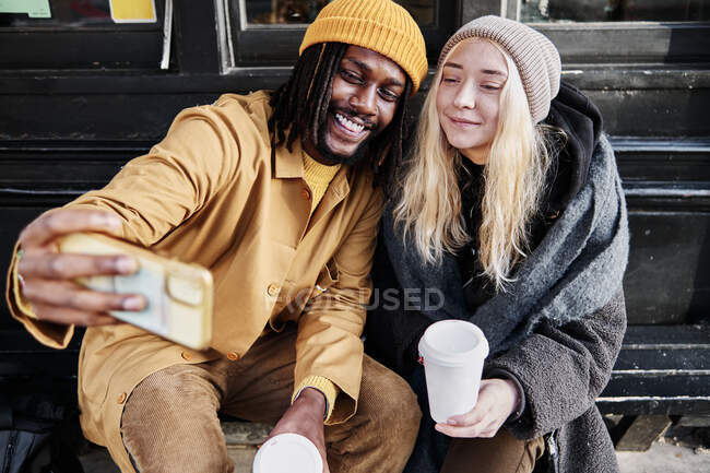 Cool biracial friends taking a selfie smiling while sitting outside, holding their cup of coffee — Stock Photo
