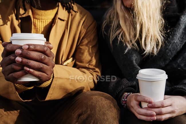 Amici multiculturali irriconoscibili in possesso di una tazza di carta di caffè mentre seduti insieme per strada. concentrarsi sulle mani. — Foto stock