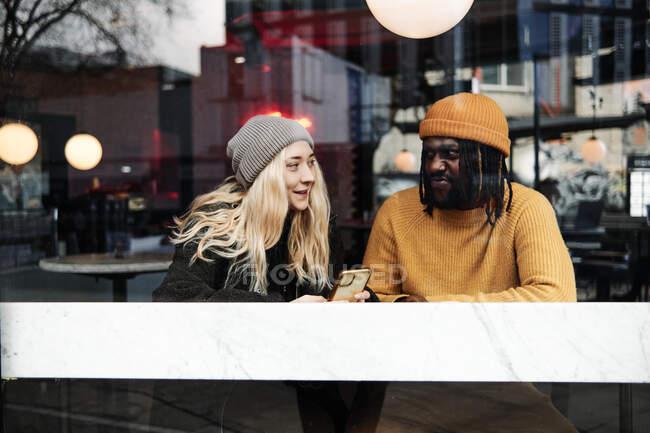 Jeune couple biracial moderne parlant à la fenêtre d'un café, reflet de la ville sur le verre — Photo de stock