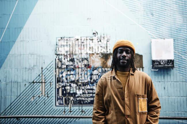 Joven africano de moda de pie frente a la pared de colores, mirando a la cámara con una sonrisa. espacio de copia - foto de stock