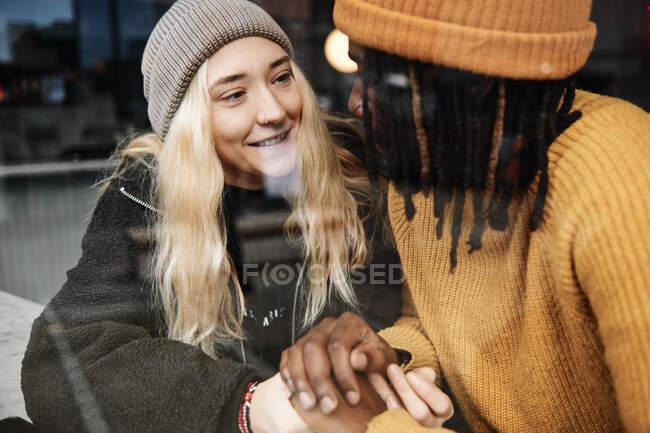 Heureux couple biracial souriant à l'autre tenant la main tout en étant assis à la fenêtre d'un café avec reflet de la rue — Photo de stock