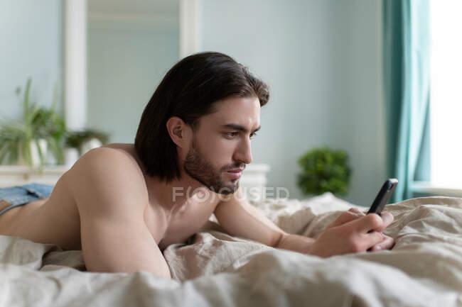 Giovane uomo sdraiato sul letto e utilizzando il telefono cellulare nel fine settimana mattina a casa — Foto stock