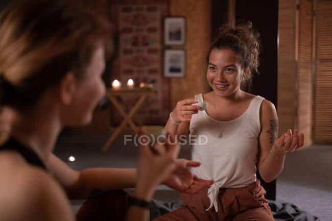 Feliz feminino sorrindo e conversando com professor de ioga durante cerimônia de chá em estúdio — Fotografia de Stock
