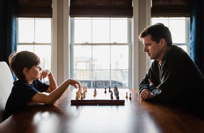Отец и сын сидят за столом и играют в шахматы.. — стоковое фото