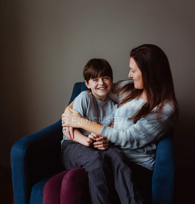 Happy woman hugging her smiling son as he sits in her lap on a chair. — Stock Photo
