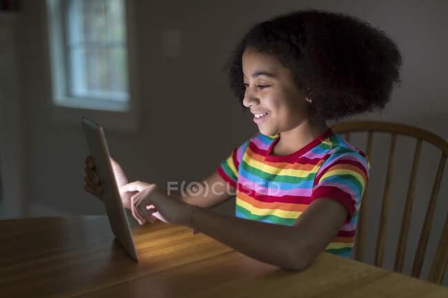 Посмішка десятирічна бірасова дівчинка працює над ipad за столом. — Stock Photo
