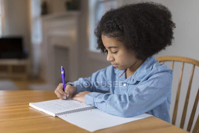 Ten year-old bi-racial girl doing homework at table — стокове фото