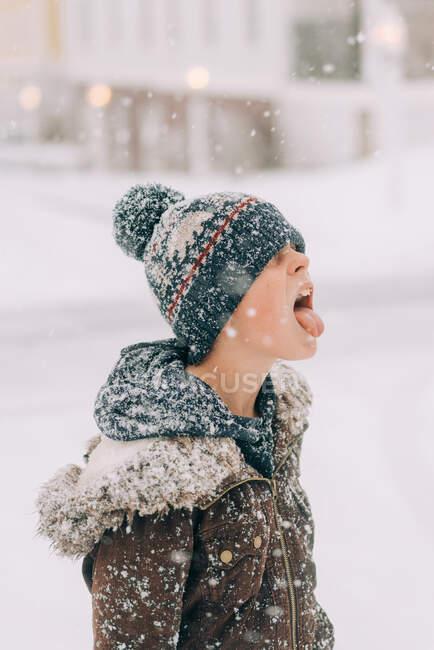 Ragazzo con cappello lanoso cattura fiocco di neve sulla lingua — Foto stock