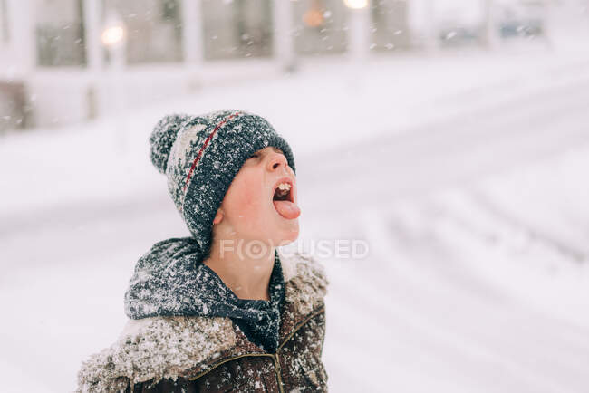 Boy with woolly hat catching snow flake on his tongue — Stockfoto