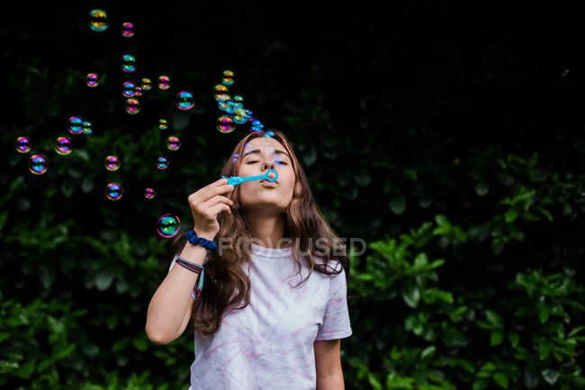 Adolescente sopra bolhas ao ar livre com cores e atividades iridescentes — Fotografia de Stock