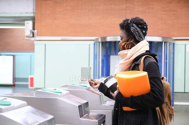 University female african student wearing protective face mask passing through the turnstiles with her transport card at the underground station. New normal in public transport. — Stock Photo