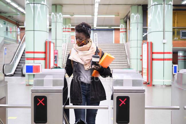 Étudiante africaine de l'université portant un masque protecteur passant par les tourniquets avec sa carte de transport à la station de métro. Nouveau normal dans les transports publics. — Photo de stock