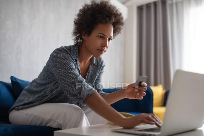 Чорна жінка користується ноутбуком і кредитною карткою, щоб робити покупки на дивані вдома. — стокове фото