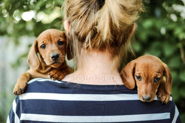 Mujer con cachorros de pie al aire libre - foto de stock