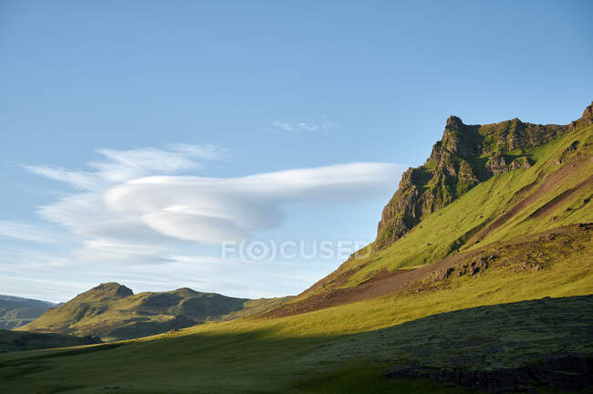 Majestic valley with endless green highlands and mountains peak under clear blue sky — Stock Photo
