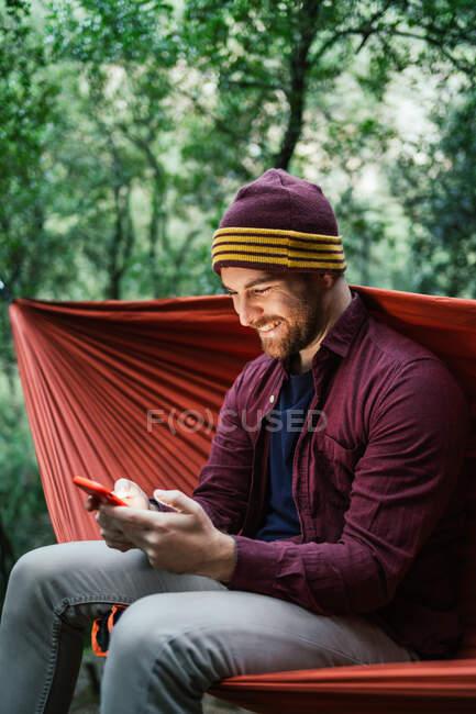 Молодий самець використовує свій смартфон на гамаку в лісі. — стокове фото