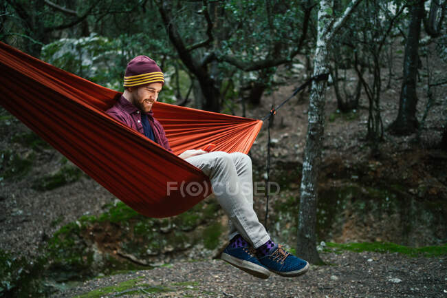 Junger Mann ruht mit seinem Smartphone auf einer Hängematte im Wald — Stockfoto