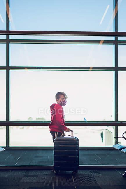 Giovane ragazzo che tiene la valigia in piedi accanto alla finestra in aeroporto. — Foto stock