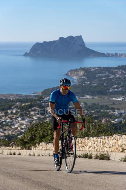 Ciclista escalando la colina Cumbre del Sol con vista al mar Mediterráneo y Calpe detrás, Costa Blanca, provincia de Alicante, España - foto de stock