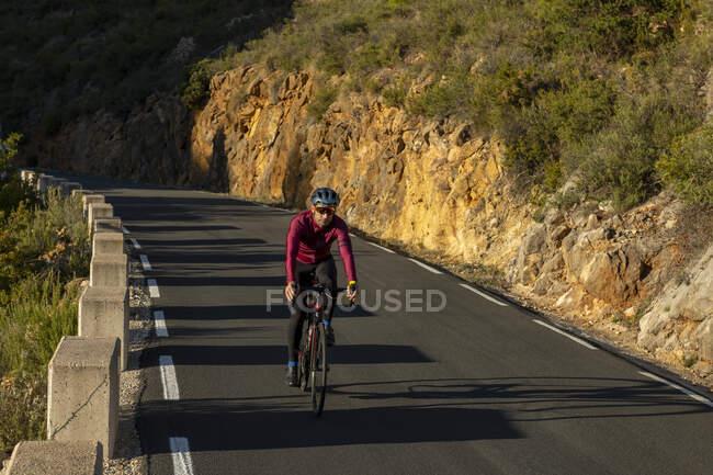 Человек на велосипеде по горной дороге от Бениссы до деревни Пинос, Коста Бланка, провинция Аликанте, Испания — стоковое фото