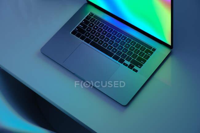 Портативный компьютер с ярким экраном, стоящим на столе, с низким ключом синего света изображения. Концепция работы дома, синий свет, минималистичный рабочий стол — стоковое фото