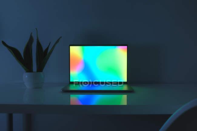Ordinateur portable avec scène vibrante debout sur une table, image basse lumière bleue. Concept de travail à la maison, lumière bleue, bureau minimaliste — Photo de stock