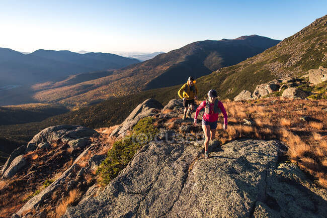 Man and woman trail running in mountains in morning — Stock Photo