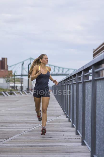 Блондинка бежит по городской набережной, Монреаль, Квебек, Канада — стоковое фото