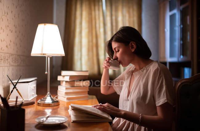 Молодая женщина потягивает горячий напиток и читает книгу во время учебы вечером дома — стоковое фото
