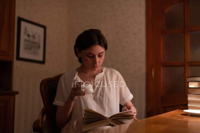 Молодая женщина с чашкой горячего напитка наслаждается чтением вечером дома — стоковое фото