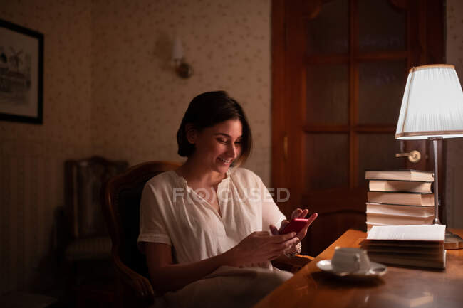 Счастливая молодая женщина улыбается и просматривает мобильный телефон во время чтения книг вечером — стоковое фото