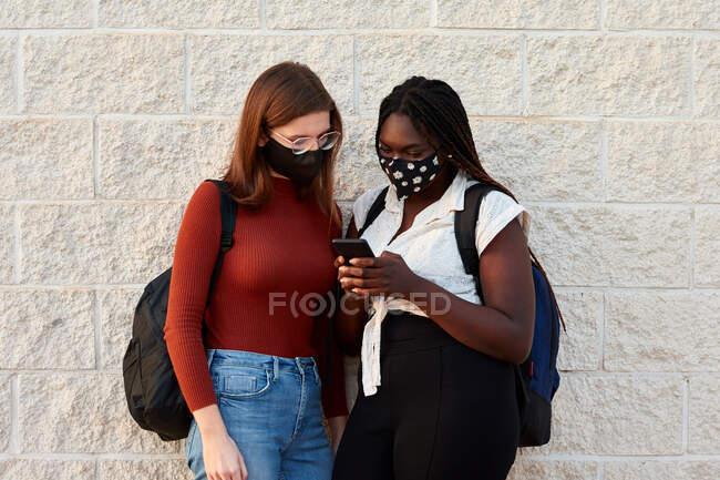 Две молодые женщины в маске смотрят на свой смартфон. — стоковое фото