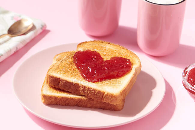 Toasts with heart shaped strawberry jam on it as a concept for love and Valentines Day — Stock Photo