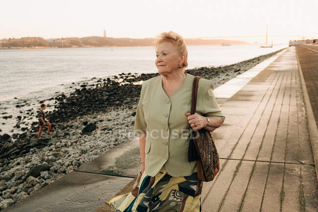 Elder woman standing alone at the riverside in Lisbon — Stock Photo