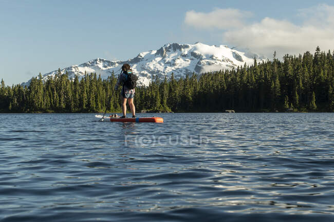 Anonymous female hiker paddleboarding on lake near mountain slope and green forest — Stock Photo