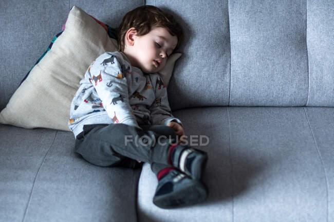 Foto frontal de un niño pequeño durmiendo en el sofá gris. - foto de stock