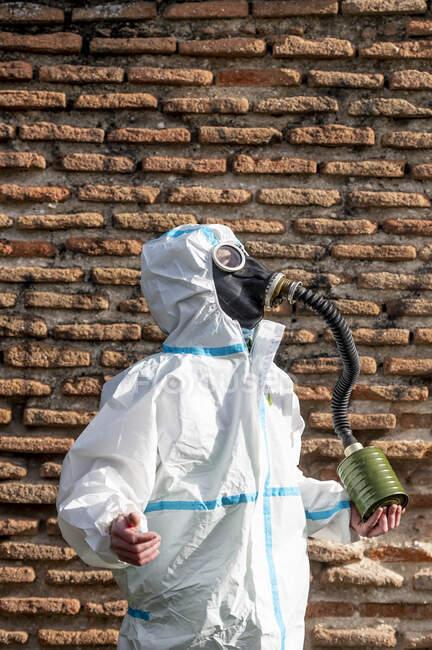 Un hombre con un traje del virus EPI y una máscara de gas en la cara con la ciudad en el fondo - foto de stock