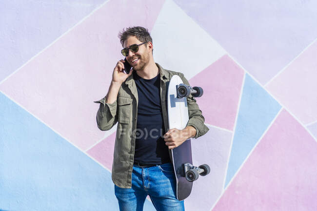 Young man with his skate talking from his smartphone — Stock Photo