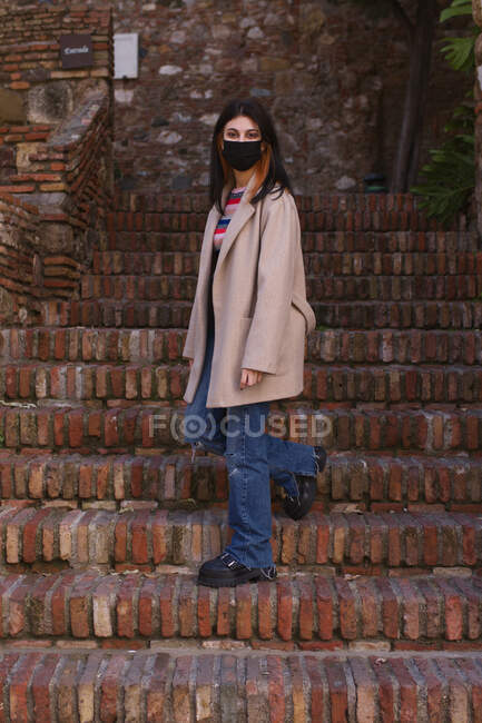 Natural young woman with mask descending the stairs of an old urban construction — Stock Photo