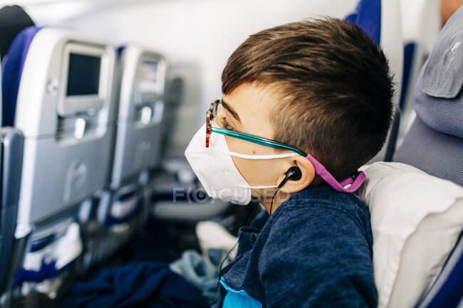 Хлопчик з окулярами, маскою, навушники дивляться на сірники під час польоту. — стокове фото