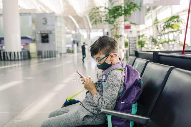 Ragazzo che indossa occhiali e maschera usando il cellulare seduto sul terminal dell'aeroporto — Foto stock