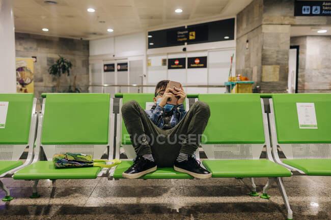 Мальчик-подросток в маске с телефона в терминале аэропорта — стоковое фото
