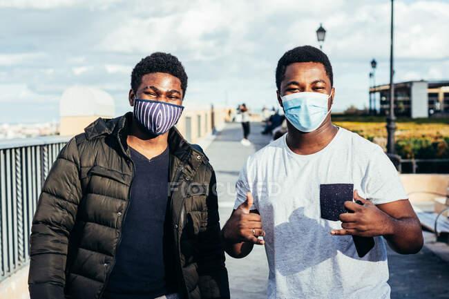 Retrato de dois amigos afro-americanos com máscaras posando alegremente em um espaço urbano. — Fotografia de Stock