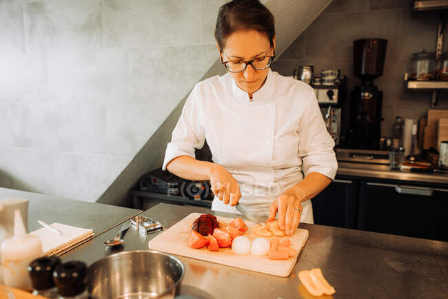 Female chef cutting vegetables in restaurant kitchen — Stock Photo