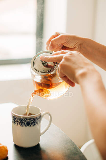 Female hands pouring hot tea in cup — Stock Photo