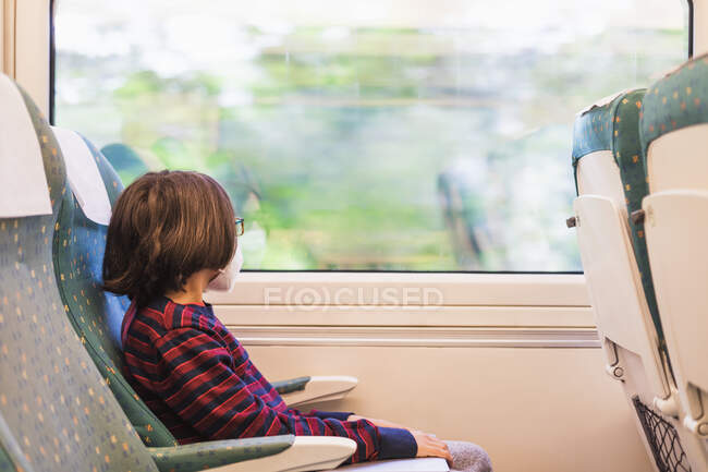 Young male tourist wearing mask traveling by train — Stock Photo