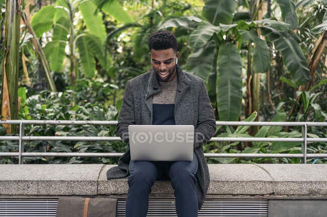 Empresário Afro trabalhando no laptop na rua — Fotografia de Stock